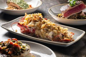 Baked Gulf of Maine lobster with shrimp and scallop stuffing, along with some other smaller plates surrounding it.