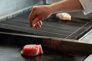 Chef sprinkling sale on raw tuna that was just set on the grill to cook.