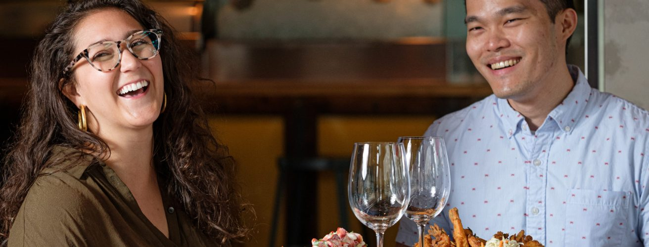 Woman and man in their late twenties laughing with empty glasses and variety of food.