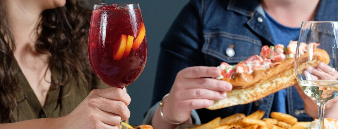 Two women drinking sangria and eating a cold lobster roll.