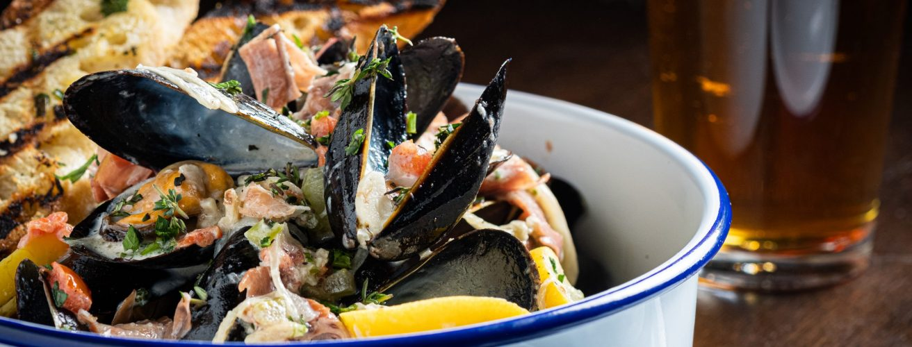 White bowl with organic PEI mussels in traditional garlic-butter broth with grilled crusty bread.