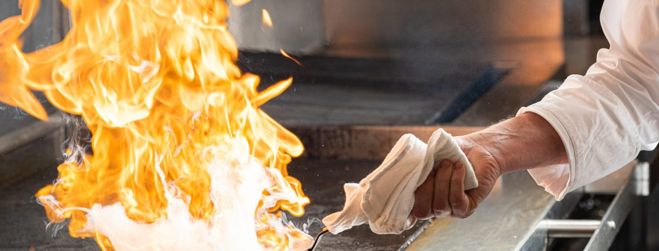 Chef flipping wok filled with fire.