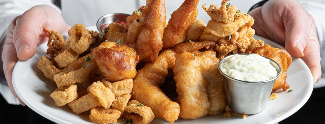 Chef holding fisherman's platter including colossal naked shrimp, sea scallops, local whitefish and calamari.